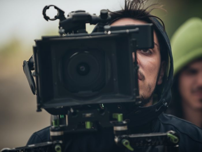 Man using film camera. Another man in green hood in background