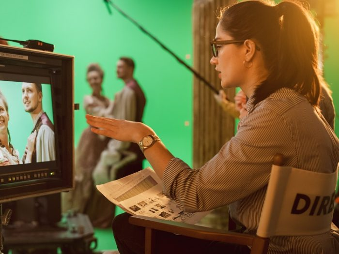 Female director sat in chair looking at a scene on a screen. Male and female actors in background